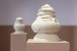 Pierwszy plan fotografii zajmuje białe naczynie w kształcie przypominającym wazę, ustawione na jasnobeżowym postumencie. W rzeczywistości jest to forma wydrukowana na drukarce 3D, stylizowana na urnę z czasów kultury pomorskiej. W głębi, po lewej stronie kadru, stoi kolejny beżowy kubik z białym naczyniem, co stanowi nieostry, dalszy plan.