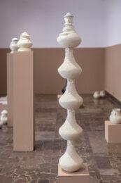 Zdjęcie przedstawia białe naczynia ustawione w różnych miejscach w sali wystawowej. Niektóre stoją bezpośrednio na podłodze, inne na beżowych postumentach – niskich lub wysokich. W środku pierwszego planu uchwycono wysoką konstrukcję złożoną ze stojących jedno na drugim białych naczyń, które razem tworzą rodzaj kolumny.
