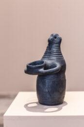 Tematem zdjęcia jest wspomniana wcześniej czarna rzeźba ustawiona na beżowym postumencie. Obiekt ma kształt człowieka trzymającego przed sobą, obydwoma rękoma, naczynie. Figurka przypomina eksponat z muzeum archeologicznego.