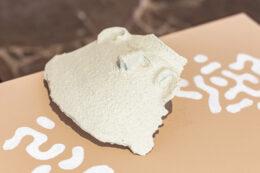 """Zdjęcie przedstawia biały, płaski obiekt leżący na beżowym postumencie pomalowanym w białe wzory. Jest to rodzaj maski z """"wyrzeźbioną"""" ludzką twarzą, może to być również część naczynia, np. urny. Przedmiot budzi skojarzenia z artefaktami pochodzącymi z wykopalisk archeologicznych."""