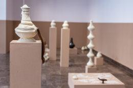 Zdjęcie przedstawia szerszy widok ekspozycji. W kadrze mieści się kilka obiektów, a są to głównie białe naczynia na wyższych lub niższych postumentach. Naczynie na pierwszym planie, po lewej stronie, wyróżnia się zawieszonym, długim puklem włosów, który został oprawiony w metalową skuwkę.