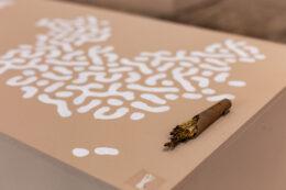 Fotografia przedstawia górną powierzchnię beżowego postumentu, gęsto ozdobioną białymi wzorami. Na tej powierzchni leży wiązka nadpalonych ziół, używanych zapewne jako kadzidło.