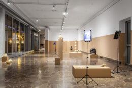 Zdjęcie przedstawia widok ogólny wystawy w dolnej sali galerii. Uchwycono na nim zarówno obiekty (formy z drukarki 3D, postumenty, stojaki z tabletami), jak i samo wnętrze pomieszczenia z oknami po lewej stronie i ścianą po prawej i w głębi, na wprost. Dominującym kolorem jest jasny beż.