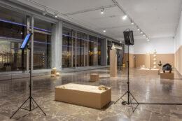 """Zdjęcie przedstawia ogólny widok wystawy w dolnej sali galerii. Kadr obejmuje naczynia umieszczone bezpośrednio na podłodze oraz postumenty, na których ustawiono różnorodne obiekty. Na wystylizowanej na archeologiczną ekspozycji umieszczone zostały także tablety na wysokich stojakach. Dzięki nim ta pozornie """"tradycyjna"""" wystawa jest dostępna także w tzw. rzeczywistości rozszerzonej."""