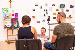 Fotografia przedstawia trzy osoby, z których dwie siedzą zwrócone plecami do obiektywu aparatu, a twarzami do siedzącej na podłodze przed nimi postaci, której twarz i ramiona są widoczne. Młoda kobieta, będąca portrecistką, uśmiecha się do siedzących, trzymając w dłoniach biały blok rysunkowy. W głębi, po lewej, stoi sztaluga z kolorowymi rysunkami stanowiącymi zabawne portrety różnych osób. W tle, na białej ścianie, zawieszono wiele kolorowych prac.