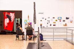 """Zdjęcie przedstawia kolejny widok ogólny wystawy w dużej sali. W centralnej części siedzą trzy postacie uczestniczące w sesji portretowej. W głębi, po lewej stronie, stoi mężczyzna zwiedzający wystawę, a tuż za nim zwisa duży obiekt uszyty z kolorowych tkanin. Po prawej stronie – na białej ścianie – wiszą liczne, małe, kolorowe prace, nad którymi umieszczono napis: """"Sandra"""", będący nazwą galerii, która gościnnie prezentuje swoje dzieła."""