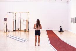 Kolejny widok ogólny z ekspozycji na piętrze. Na środku, plecami do widza, stoi dziewczyna patrząca przed siebie. Jest bosa, ubrana w koszulkę bez rękawów i szorty. Ma długie włosy zwisające na plecy, prawie do pasa. Po jej prawej stronie rozciąga się wąski czerwony dywan, a w głębi, po lewej, stoi wspominana już parokrotnie konstrukcja z ram.