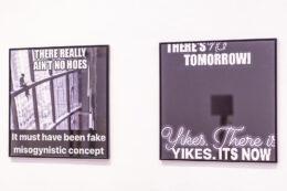 """Zdjęcie przedstawia fragment ekspozycji. Na białej ścianie wiszą dwie oprawione w czarne wąskie ramy fotografie. Obie są czarno-białe, w takim samym kwadratowym formacie. Na ich powierzchniach, jak na plakatach, widnieją białe napisy w języku angielskim. Mają one charakter kontestujących, pesymistycznych haseł – np. """"There is no tomorrow!"""" (Jutra nie będzie!)."""