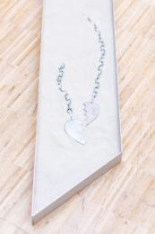 Tematem tej fotografii jest przedmiot w rodzaju dużego naszyjnika. Na białym tle, jakby usypanym z piasku leżą dwa fragmenty grubego, metalowego łańcucha. Każdy z nich zakończony jest metalową przywieszką w kształcie połówki serca. Całość znajduje się w podłużnej, zakończonej ostrą krawędzią ramie, leżącej na parkietowej podłodze.