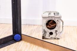 Zdjęcie przedstawia detale wspominanej wcześniej instalacji w formie budowlanej konstrukcji. Tym razem uwagę zwraca leżący na podłodze kłębek niebieskiego sznurka lub włóczki oraz dziwny pojemnik z otworami, kojarzący się z atrapą małej pralki automatycznej. We wnętrzu obiektu umieszczono pogniecioną brązową tkaninę.