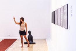 Fotografia prezentuje fragment wystawy, na tle której stoi dziewczyna ubrana w koszulkę bez rękawów i szorty. Stoi boso na parkiecie, jedna jej ręka jest uniesiona z palcem wskazującym zwróconym w stronę sufitu. Za dziewczyną, na podłodze, znajduje się siedząca gumowa lalka. Twarz dziewczyny widoczna jest z profilu.