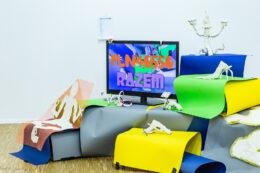 """Zdjęcie przedstawia rozległą, kolorową instalację, złożoną z wielu elementów. W środku jest płaski telewizor na nóżce, na którego ekranie wyświetlają się napisy: """"PLN 40550"""" oraz """"RAZEM"""". Obok ekranu jak i pod nim widzimy skomplikowaną konstrukcję z powyginanych arkuszy kolorowych papierów oraz małych białych przedmiotów o bardziej lub mniej abstrakcyjnych kształtach."""