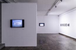Zdjęcie przedstawia widok ogólny wystawy w sali dolnej Galerii Arsenał. Po lewej stronie znajduje się białą ściana, na której zawieszony jest ekran z czarno-białą projekcją. Drugi taki ekran, również z projekcją, umieszczony jest w głębi, na białej ścianie. Po prawej stronie, w głębi, wisi 5 oprawionych czarno-białych fotografii. Dużą część zdjęcia zajmuje szara, wzorzysta podłoga.