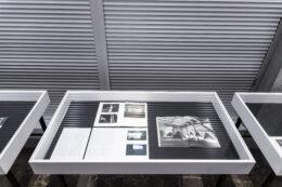 Zdjęcie przedstawia trzy gabloty, fotografowane z góry, ale tylko zawartość środkowej mieści się w kadrze w całości. Pozostałe są przedstawione jedynie w małych fragmentach. W środkowej gablocie leżą rozłożone wydruki i otwarte publikacje.