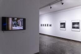 Na pierwszym planie fotografii uchwycony jest ekran z projekcją filmu dokumentalnego. Film jest kolorowy. Głębiej, po prawej stronie, zdjęcie przedstawia wspominane już kilkakrotnie oprawione czarno-białe fotografie wiszące na ścianie.