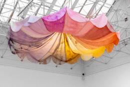Zdjęcie przedstawia kolorową draperię w kształcie fantazyjnego, okrągłego baldachimu lub może bardziej czaszy parasola ogrodowego. Obiekt jest zawieszony pod sufitem, przyczepiony został do podwieszonej metalowej konstrukcji, stanowiącej stały element sali górnej Galerii Arsenał. Użyte tkaniny mają pastelowe kolory: różowe, liliowe i żółte.