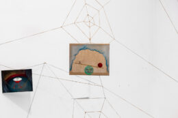 Tematem fotografii są dwa małe obrazy wiszące w przestrzeni, zawieszone na sznurkach tworzących pajęczyny. Przedstawiają baśniowe światy w surrealistycznym klimacie. Na jednym namalowane jest czerwone naczynie kroczące na długich cienkich nogach, a na drugim uśmiechnięta tarcza księżyca stanowiąca podstawę dla równoważnej huśtawki.