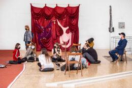 Tematem zdjęcia jest grupa osób siedzących na wystawie. Tylko dwie z nich siedzą na krzesłach, reszta na poduszkach położonych na podłodze. Na kolanach dziewczyny siedzi mały piesek. Za grupą, przechodzi kobieta z plecakiem. Tło stanowi wielka, drapowana kotara.