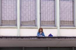 Zdjęcie przedstawia boczną ścianę Galerii Miejskiej Arsenał z zewnątrz. Na daszku pod oknami górnych pomieszczeń siedzi dziewczyna i czyta do mikrofonu tekst z kartki. Ubrana jest na niebiesko, ma jasne kręcone włosy. Obok niej stoi niebieski plecak z różowymi lamówkami. Nad nią znajdują się wysokie okna z kratami.
