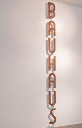 Fotografia przedstawia jedną z prac zakupionych w 2020 roku do Kolekcji Galerii Miejskiej Arsenał. Jest to Bauhaus Rafała Jakubowicza. Praca złożona jest z metalowych pojedynczych liter tworzących w pionie napis: BAUHAUS. Pokryte rdzą litery przymocowane są do białej ściany.