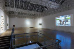 Zdjęcie przedstawia widok ogólny wystawy w dużej sali galerii. Pierwszy plan zajmuje fragment klatki schodowej z balustradą i schodami. Głębiej, po lewej stronie widzimy instalację rzeźbiarską Pawła Matyszewskiego, złożoną z kamiennych kobiecych piersi zawieszonych na ścianie. Po prawej stronie widoczny jest slajd, będący częścią pracy Franciszka Orłowskiego. Znaczną część zdjęcia zajmuje podwieszany sufit stanowiący białą, metalową, ażurową konstrukcję.