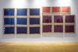 Tematem fotografii jest dzieło Jarosława Kozłowskiego, na które składa się 18 akwarel. Tworzą one dużą grupę złożoną z trzech zbiorów wyróżniających się kolorem. Od lewej jest to 9 obrazów ciemnoniebieskich, potem 6 fioletowych, a nad fioletowymi zawieszone są 3 różowe. Wszystkie oprawione są w szkło i drewniane ramy. W szybach fioletowych akwarel odbijają się wiszące naprzeciw prace Izabelli Gustowskiej.