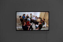 Fotografia przedstawia ekran z projekcją filmu Jany Shostak. Płaski ekran zawieszony jest na popielatej ścianie. Uchwycony na zdjęciu kadr z filmu przedstawia grupę 11 osób rozmawiających ze sobą. Wśród nich jest również artystka Jana Shostak. Osoby są w różnym wieku, kolorowo ubrane. Siedzą w kole, bardzo blisko siebie, na białych, niskich krzesełkach lub szarej kanapie.