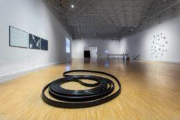 Fotografia prezentuje widok ogólny wystawy. Na pierwszym planie wyeksponowana jest praca Jana Domicza w formie zwiniętej gumowej poręczy do ruchomego chodnika. Czarna guma układa się w kształt podobny do spirali. Tłem dla niej jest jasny parkiet podłogi.